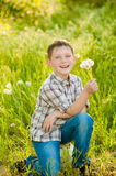 Boy on summer nature with dandelions Royalty Free Stock Images