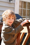 Boy in the sun. Brown haired boy in the sun on the deck Stock Images