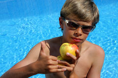 Boy with sun glasses presenting an apple Royalty Free Stock Photography