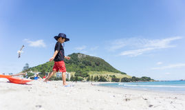 Boy in sun hat walks down Mount Maunganui beach. Royalty Free Stock Photos