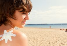 Boy with sun lotion on shoulder Stock Photo