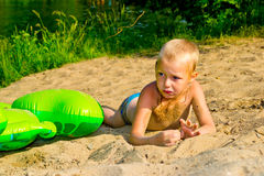Boy sunbathes on the sand Royalty Free Stock Photography