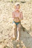 Boy sunbathes on the sand Stock Images