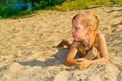 Boy sunbathes on the sand Royalty Free Stock Photos