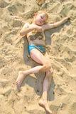 Boy sunbathes on the sand Royalty Free Stock Photo