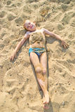Boy sunbathes on the sand Stock Photography