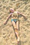Boy sunbathes on the sand Stock Photography
