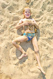 Boy sunbathes on the sand Royalty Free Stock Photo