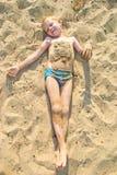 Boy sunbathes on the sand Stock Image