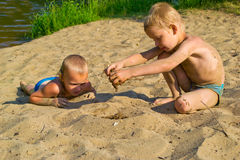 Boy sunbathes on the sand Royalty Free Stock Images