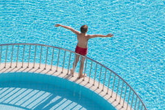 Boy sunbathing on the edge of the pool Stock Photos