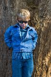Boy in sunglasses. Young boy in denim clothes and sunglasses leaning against tree Stock Images
