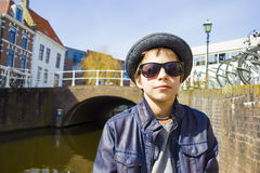 Boy in sunglasses against canal background. Handsome boy in sunglasses against canal background Stock Images