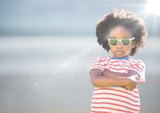 Boy in sunglasses arms folded against blurry beach with flare. Digital composite of Boy in sunglasses arms folded against blurry beach with flare Stock Photography