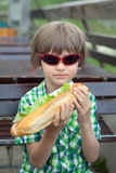 The boy in sunglasses with a great sandwich Stock Images
