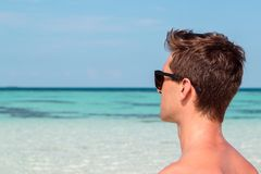 Three quarter picture of a young man on the beach looking at the clear blue sea royalty free stock photos
