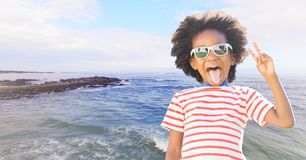 Boy in sunglasses making peace sign against coastline with flare Royalty Free Stock Photos