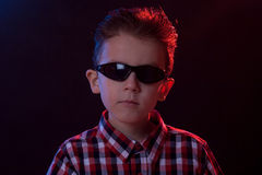 Boy with sunglasses in party lights Royalty Free Stock Photos