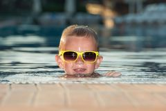 The boy with sunglasses resting in the pool.Summer vacation. stock image
