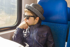 Boy in sunglasses rides on a train Stock Photo