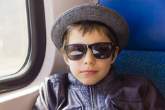 Boy in sunglasses rides on a train Stock Photos