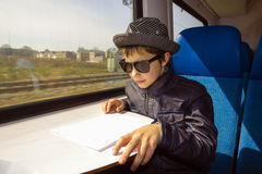 Boy with sunglasses rides on a train. Handsome boy with sunglasses rides on a train reading from the paper Royalty Free Stock Images