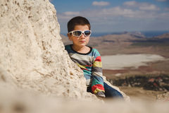 Boy in sunglasses sits on the top Stock Photography