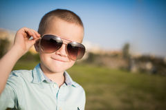 Boy in sunglasses smiling. Beautiful smiling boy and holding sunglasses Stock Photos