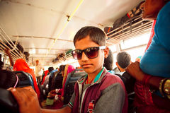 Boy in sunglasses standing inside crowded bus Stock Photography