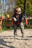 Boy with sunglasses on swing Stock Image