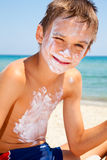 Boy with sunscreen on face. Child applied too much of sunblock cream Royalty Free Stock Photography
