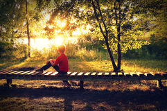 Boy at sunset, artistic toned image. Boy sitting on bench, mood concept royalty free stock photos