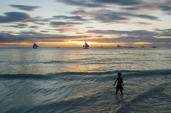 Boy at sunset coast. A boy in the waves at sunset Royalty Free Stock Photo
