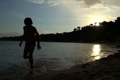 Boy in sunset sea Royalty Free Stock Images