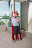 Boy in super hero costume standing with arm raised on sofa bed at home Royalty Free Stock Images