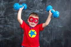 Boy superhero with dumbbells Royalty Free Stock Photos