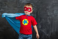 Boy superhero in a blue Cape red mask and a red t-shirt with a star royalty free stock photo