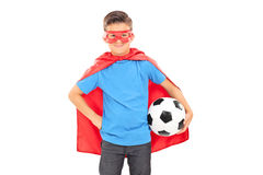 Boy in superhero costume holding a football Stock Image