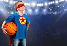A boy in a superhero costume plays basketball. stock photography