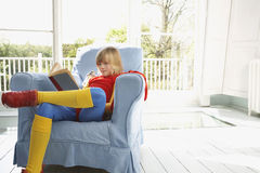 Boy In Superhero Costume Reading Book In Armchair Royalty Free Stock Photo