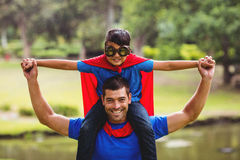Boy in superhero costume sitting on fathers shoulder Stock Photos