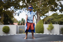 Boy in superhero costume standing on trampoline Royalty Free Stock Photography