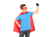 Boy in superhero costume taking a selfie. Isolated on white background Royalty Free Stock Photos