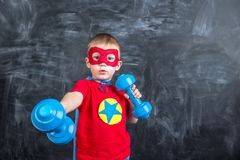 Boy superhero with dumbbells Royalty Free Stock Image