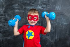 Boy superhero with dumbbells Royalty Free Stock Photo