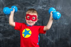 Boy superhero with dumbbells Stock Image