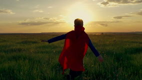 Boy superhero in a field at sunset