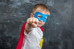 Boy superhero in a white shirt showing fist royalty free stock images