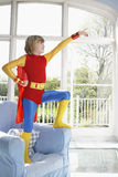 Boy In Superman Costume On Armchair Pointing Up Stock Photo