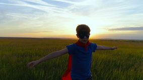 A boy in a superman costume runs across the green field at sunset stock video footage